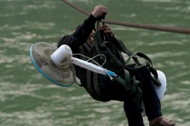 A villager carries an electric fan while zipping across the Nu River in Nujiang Lisu Autonomous Prefecture in Yunnan province, China, March 28, 2018. Picture taken March 28, 2018. REUTERS/Aly Song