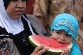 A mother holds her child eating a watermelon during prayers for the Muslim holiday of Eid Al-Adha at Sunda Kelapa port in Jakarta,  Indonesia September 1, 2017.  REUTERS/Beawiharta
