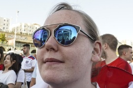 BRIGHTON, ENGLAND – JULY 03: The big screen is reflected in a fans sunglasses as she watches the FIFA 2018 World Cup Finals match between Colombia and England at Luna Beach Cinema on Brighton Beach on July 3, 2018 in Brighton, England. World Cup fever is building among England fans after reaching the Round of 16 in Russia. (Photo by Alan Crowhurst/Getty Images)