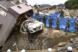 Rescue workers look for missing people in a house damaged by heavy rain in Kumano town, Hiroshima Prefecture, Japan, in this photo taken by Kyodo July 9, 2018. Mandatory credit Kyodo/via REUTERS ATTENTION EDITORS – THIS IMAGE WAS PROVIDED BY A THIRD PARTY. MANDATORY CREDIT. JAPAN OUT. NO COMMERCIAL OR EDITORIAL SALES IN JAPAN.     TPX IMAGES OF THE DAY