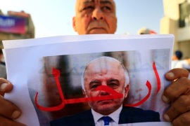 A protester holds a picture of Iraqi Prime Minister Haider al-Abadi with
