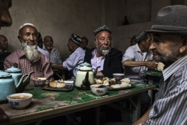 KASHGAR, CHINA – JULY 1: Ethnic Uyghur men talk as they meet at a teahouse  on July 1, 2017 in the old town of Kashgar, in the far western Xinjiang province, China. Kashgar has long been considered the cultural heart of Xinjiang for the province's nearly 10 million Muslim Uyghurs. At an historic crossroads linking China  to Asia, the Middle East, and Europe, the city has  changed under Chinese rule with government development, unofficial Han Chinese settlement to the w
