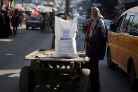 A Palestinian man stands next to a cart carrying a flour sack distributed by the United Nations Relief and Works Agency (UNRWA) in Khan Younis refugee camp in the southern Gaza Strip January 3, 2018. REUTERS/Ibraheem Abu Mustafa