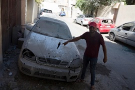 epa06991882 A man looks at a damaged car after rockets fired by unknown militants landed on the residential area of Ben Ashour, Tripoli, Libya, 01 September 2018 (issued 02 September 2018). According to reports, rockets hit several parts of Tripoli on 01 September including the Al-Waddan Hotel, which is only 100 meters away from the Italian embassy, and Ben Ashour area near prime minister's office as fighting renewed between rival factions in the capital. At least 39 people, including civilians, were killed in the fresh clashes that erupted over the past few days. EPA-EFE/STR