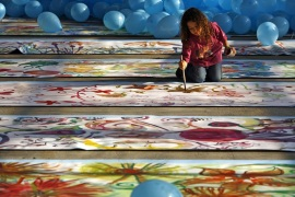 A child paints a flower on the world's longest painting ever made by children, in Bucharest November 18, 2006. A Guinness World Records representative who was at the scene confirmed the record at the event, which was organised by the United Nations Children's Fund (UNICEF). REUTERS/Bogdan Cristel (ROMANIA)