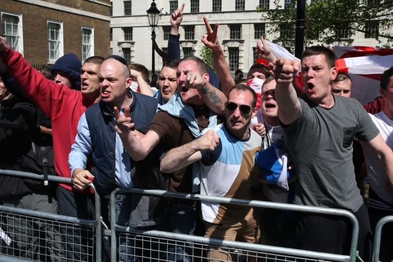 LONDON, UNITED KINGDOM – MAY 27:  Protesters with the English Defence League gesture towards a counter demonstration held by the group Unite Against Facism in Whitehall outside Downing Street on May 27, 2013 in London, England. The EDL are protesting what the group sees as a lack of support and protection given to British troops following the terror attack last week, in which soldier Drummer Lee Rigby was murdered in a knife and machete attack by two Muslim men outside Woolwich Barracks.  as tensions run high across certain communities. (Photo by Peter Madiarmid/Getty Images)