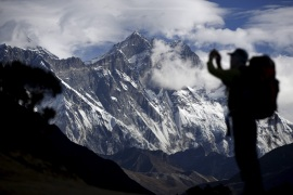 A tourist is silhouetted as he takes pictures of Mount Nuptse (C) as Mount Everest (L) is covered with clouds in Solukhumbu district, also known as the Everest region, in this picture taken November 30, 2015. To match Insight QUAKE-NEPAL/SHERPAS      REUTERS/Navesh Chitrakar