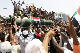 Sudanese demonstrators ride atop a military tanker and wave their national flags as they protest against the army's announcement that President Omar al-Bashir would be replaced by a military-led transitional council, near Defence Ministry in Khartoum, Sudan April 12, 2019. REUTERS/Stringer