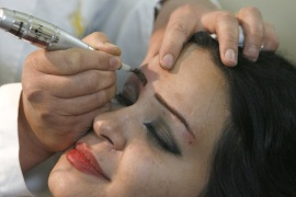 Iraqi beautician Ina'am Hikmet tattoos a client's eyebrows in Baghdad May 3, 2009. Picture taken May 3, 2009.   REUTERS/Thaier al-Sudani (IRAQ SOCIETY)
