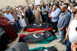People pray near coffins draped with Libyan flags, with the bodies of members of the Libyan internationally recognised government forces who were killed during clashes, during a funeral in Tripoli, Libya April 24, 2019. REUTERS/Ismail Zitouny