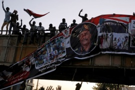Protesters tear down a banner with a picture of Sudan's head of transitional council, Lieutenant General Abdel Fattah Al-Burhan Abdelrahman and pictures of Sudanese soldiers and protesters together, minutes after it was hanged to a railroad bridge near the Defence Ministry in Khartoum, Sudan, April 20, 2019. REUTERS/Umit Bektas
