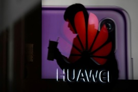A man walking past a Huawei P20 smartphone advertisement is reflected in a glass door in front of a Huawei logo, at a shopping mall in Shanghai, China December 6, 2018. REUTERS/Aly Song