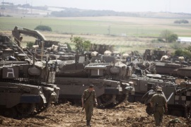 MAVKIM, ISRAEL – MAY 06:  Israeli soldiers walks in front of a Merkava tanks, stationed near the border with the Gaza Strip on May 6, 2019 in Mavkim, Israel. Palestinian leaders in Gaza agreed a ceasefire with Israel on today to end a deadly two-day escalation in violence that threatened to widen into war. (Photo by Lior Mizrahi/Getty Images)