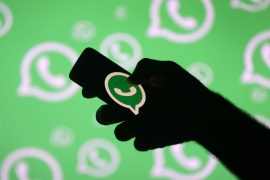 A man poses with a smartphone in front of displayed Whatsapp logo in this illustration September 14, 2017. REUTERS/Dado Ruvic