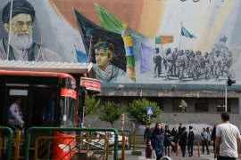 Daily life in Tehran – – TEHRAN, IRAN – MAY 22: Pedestrians pass in front of a political mural depicting Ruhollah Khomeini, founder of the Islamic republic of Iran, in Tehran, Iran on May 22, 2019.