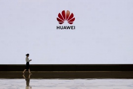 SHENZHEN, CHINA – APRIL 12: A member of Huawei's reception staff walks in front of a large screen displaying the logo in the foyer of a building used for high profile customer visits and displays at the company's Bantian campus on April 12, 2019 in Shenzhen, China. Huawei is Chinas most valuable technology brand, and sells more telecommunications equipment than any other company in the world, with annual revenue topping $100 billion U.S.  Headquartered in the southern
