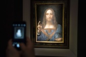 NEW YORK, NY – NOVEMBER 15: A visitor takes a photo of the painting 'Salvator Mundi' by Leonardo da Vinci at Christie's New York Auction House, November 15, 2017 in New York City. The coveted painting is set to be auctioned off on Wednesday night and has been guaranteed to sell for over $100 million.(Drew Angerer/Getty Images)== FOR NEWSPAPERS, INTERNET, TELCOS & TELEVISION USE ONLY ==