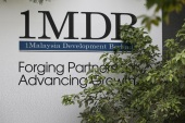 Foliage partly covers a 1 Malaysia Development Berhad (1MDB) billboard at the funds flagship Tun Razak Exchange development in Kuala Lumpur, Malaysia, July 3, 2015. Malaysian Prime Minister Najib Razak slammed a report that said close to $700 million was wired to his personal account from banks, government agencies and companies linked to the debt-laden state fund 1MDB, claiming this was a