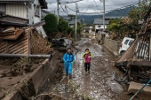 NAGANO, JAPAN – OCTOBER 15: People walk past buildings that were destroyed by Typhoon Hagibis, on October 15, 2019 in Hoyasu near Nagano, Japan. Japan has mobilised over 100,000 rescue workers after Typhoon Hagibis, the most powerful storm in decades, swept across the country killing 66 people and leaving thousands injured and homeless. (Photo by Carl Court/Getty Images)