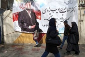People walk past a parliamentary election campaign poster in Tehran, Iran February 15, 2020. Nazanin Tabatabaee/WANA (West Asia News Agency) via REUTERS ATTENTION EDITORS – THIS IMAGE HAS BEEN SUPPLIED BY A THIRD PARTY.