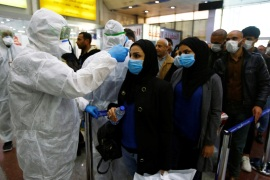 Iraqi medical staff check passengers' temperature, amid the new coronavirus outbreak, upon their arrival at Najaf airport, Iraq February 20, 2020. REUTERS/Alaa al-Marjani.