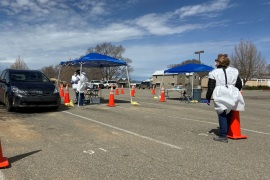 A car pulls up to a registration table at a drive-through coronavirus testing station set up in the car park of Taos High School, New Mexico on Wednesday as the state's department of health sent out a mobile testing unit to rural counties in Taos, New Mexico, U.S. March 25, 2020. REUTERS/Andrew Hay