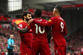 LIVERPOOL, ENGLAND – MARCH 07: Sadio Mane of Liverpool celebrates with Mohamed Salah and Roberto Firmino after scoring his team's second goal during the Premier League match between Liverpool FC and AFC Bournemouth  at Anfield on March 07, 2020 in Liverpool, United Kingdom. (Photo by Jan Kruger/Getty Images)