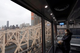 A woman in a face mask looks over an empty Queensboro Bridge while riding The Roosevelt Island Tramway from Manhattan during the outbreak of the coronavirus disease (COVID-19) in New York City, U.S., March 28, 2020.  Picture taken March 28, 2020. REUTERS/Andrew Kelly