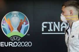 Travellers pass by a logo of the 2020 UEFA European Football Championship displayed on a wall inside Bucharest Henri Coanda International Airport, in Otopeni, Romania, March 16, 2020. Inquam Photos/Octav Ganea via REUTERS ATTENTION EDITORS – THIS IMAGE WAS PROVIDED BY A THIRD PARTY. ROMANIA OUT. NO COMMERCIAL OR EDITORIAL SALES IN ROMANIA