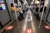 People ride a subway with social distancing signs on a floor inside a train as the spread of the coronavirus disease (COVID-19) continues, in Milan, Italy, April 27, 2020. REUTERS/Flavio Lo Scalzo