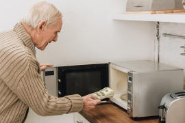 senior man with dementia disease putting dollars in microwave oven