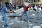 Demonstrators throw pieces of concrete during a protest against growing economic hardship in Beirut, Lebanon April 28, 2020. REUTERS/Mohamed Azakir REFILE – CORRECTING NAME OF OBJECTS THROWN