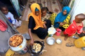 An internally displaced Somali woman and her children prepare their Iftar meal during the month of Ramadan at the Shabelle makeshift camp in Hodan district of Mogadishu, Somalia April 24, 2020. REUTERS/Feisal Omar