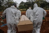 Employees carry the coffin of a person who died from COVID-19 at the Vila Formosa cemetery, in the outskirts of Sao Paulo, Brazil on May 20, 2020. – Brazil has emerged as the latest flashpoint in the coronavirus pandemic. The country has registered more than 270,000 cases and nearly 18,000 deaths so far, and the increase in infections is not expected to peak until June. (Photo by NELSON ALMEIDA / AFP)