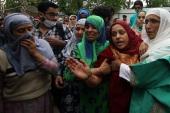 Indian soldiers shot dead a civilian in Kashmir- – BUDGAM, KASHMIR, INDIA-MAY 13: Sister (c) mourns the death of her brother Mehraj-u-din Shah, who was killed by Indian soldiers near a check point at Kawoosa,Narbal in central Kashmir's Budgam on May 13, 2020.Police said that a civilian travelling in a car jumped at two check points after which Indian paramilitary soldiers fired at him in which he got injured ,he was shifted to the hospital where doctors declared him dead on arrival. However victim's father denied the police version, saying his son did not drive through any check points and soldiers stopped him and then shot him, he said to a news agency.