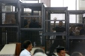 Muslim Brotherhood's General Guide Mohamed Badie is pictured in a defendant's cage with other defendants in a courtroom in Cairo