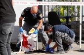 Israeli security personnel check blood-stained fabric near the scene of a suspected stabbing incident in Jerusalem