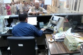 Libyan people gather in front of a counter in a bank to buy foreign currency in Misrata