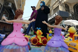 A woman wearing a face mask walks past toys for sale in Sidon
