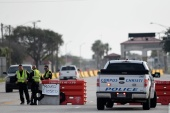 Police officers stand at a checkpoint after a shooting incident at Naval Air Station Corpus Christi