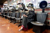 FILE PHOTO: Jessica King sits under a dryer at Three-13 Salon, Spa and Boutique, during the phased reopening of businesses and restaurants from coronavirus disease (COVID-19) restrictions in the state, in Marietta, Georgia, U.S., April 24, 2020. REUTERS/Bita Honarvar/File Photo