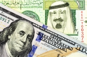 A close up image of a blue American one hundred dollar bill and a Saudi Arabian one riyal note