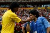 مارادونا (يمين) يقبل يد رونالدينيو (رويترز)
