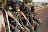 Malian soldiers ride in the back of a military pickup truck in Gao