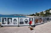 A woman walks past photos of the Cannes Film festival on the Croisette in Cannes as a lockdown is imposed to slow the rate of the coronavirus disease (COVID-19) in France