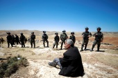 Palestinian man sits in front of Israeli troops during a protest in the Israeli-occupied West Bank