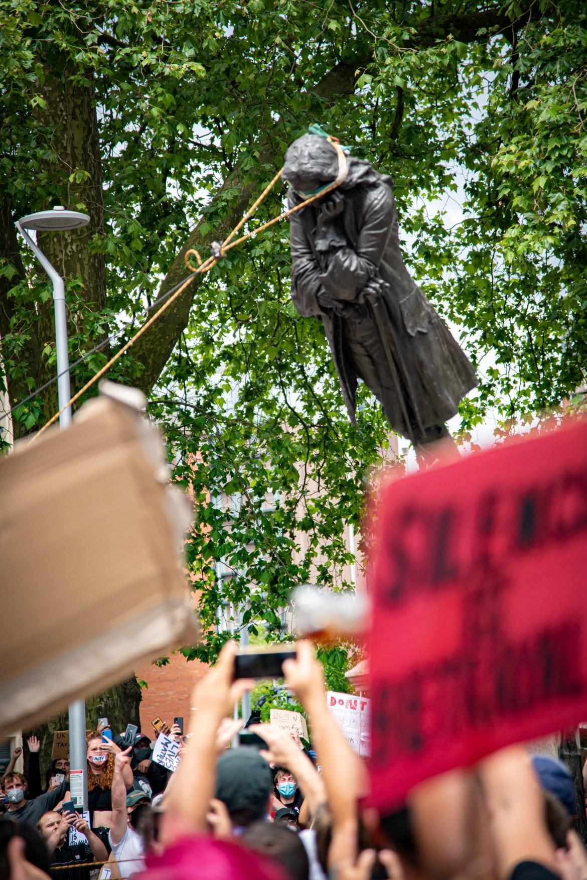 متظاهرون بريطانيون يسقطون تمثال تاجر الرقيق في القرن السابع عشر إدوارد كولستون من فوق قاعدته بمدينة بريستول