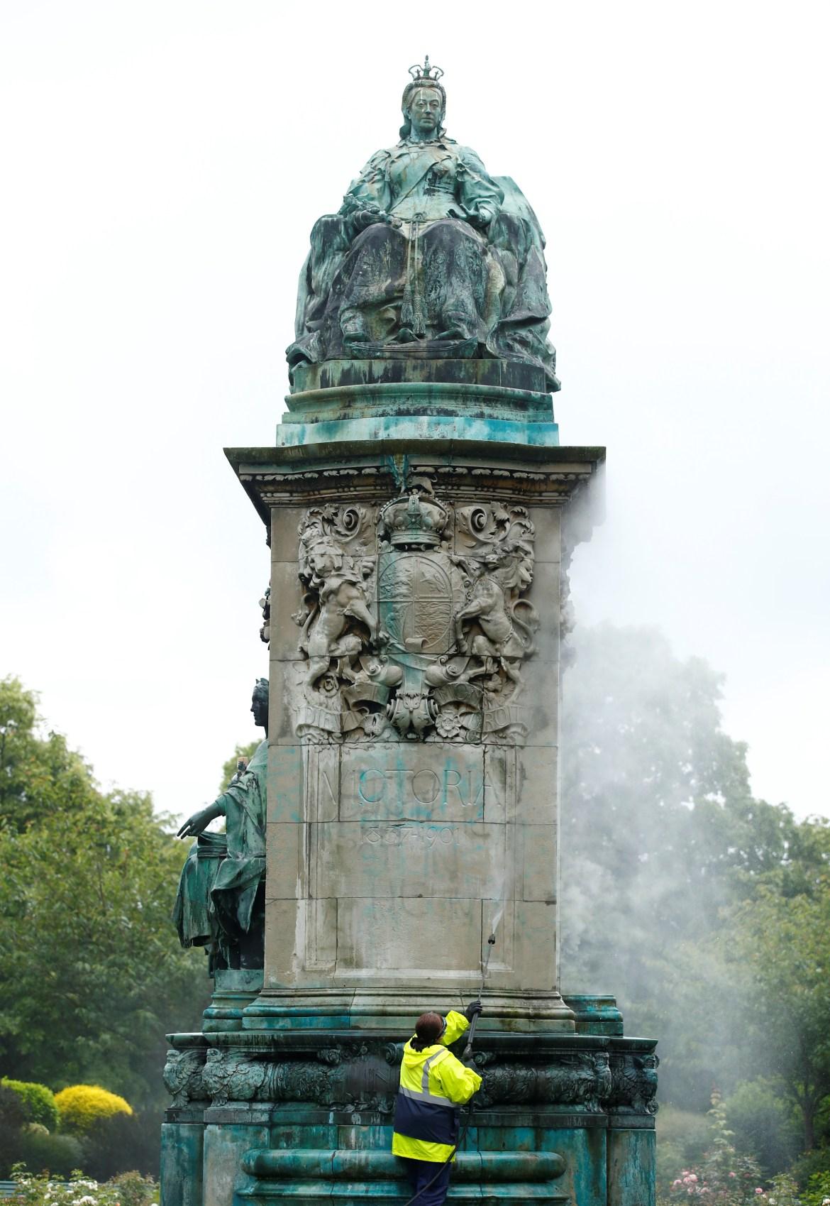 عامل في البلدية البريطانية يغسل تمثالا للملكة فيكتوريا لطخه المحتجون في مدينة ليدز