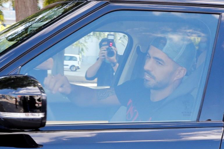سواريز يبكي في سيارته أثناء خروجه من برشلونة (رويترز)