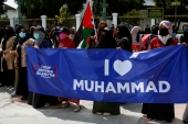 متظاهرون في جاكرتا حملوا لافتات تدعو إلى مقاطعة المنتجات الفرنسية والوقوف لنصرة النبي (الأناضول)